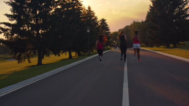 Fitness women running in park. Back view of women group running on park road video