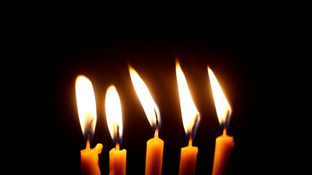 Five burning candles on black background video