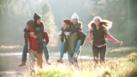 Five friends have fun piggybacking by a rural lake video
