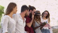 Five friends on vacation in Ibiza looking at a guidebook, shot on R3D video