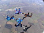 Five skydivers performing formations video