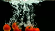Five tomatoes falling in water video