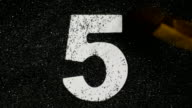 Five. Wooden number in sand. video