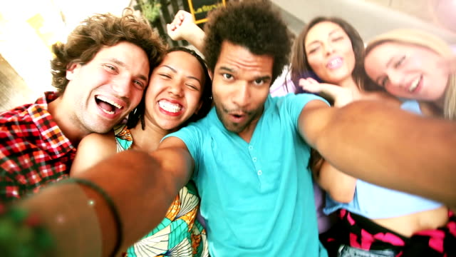 Five young adults laughing while taking a group selfie video