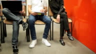 Five young people sitting on the chairs in the office video