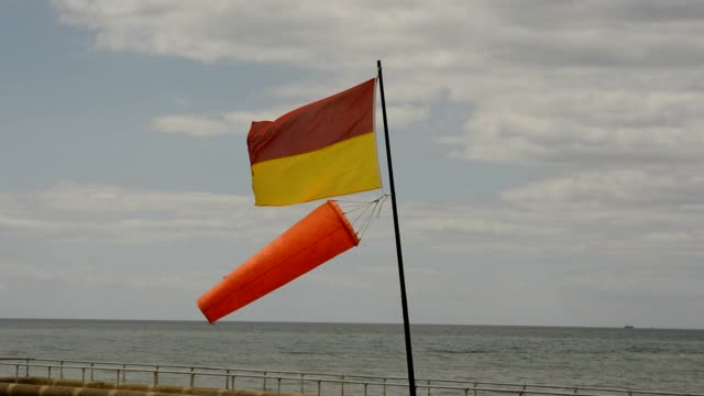 Flag and windsock on Brighton Beach, UK video