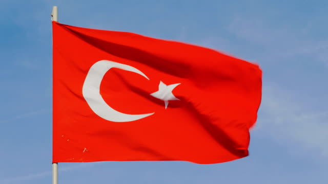 Flag of Turkey is waving on background of clear blue sky in sunny day video