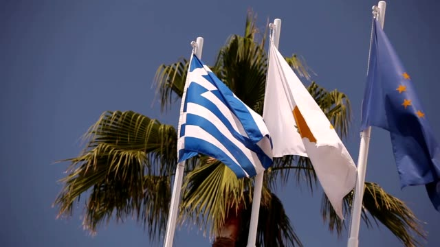 Flags of the European Union, Greece, Cyprus, the city of Aya Napa, Greece, Flags on the flagpole, the wind waving the flag, Flags on flagpole, wind waving flag, against blue sky background video