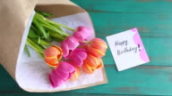 Flat lay view of Tulip flowers bouquet with Happy birthday message note video