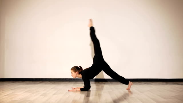 Flexible girl doing forearm stand split and scorpion pose video