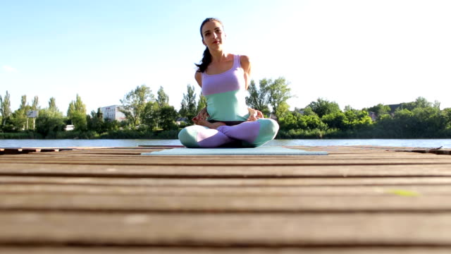Flexible girl sits in Lotus position on bridge. video