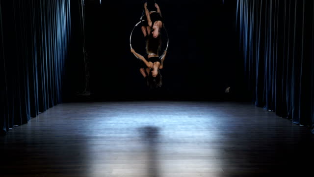 Flexible girls makes a gymnastic elements on the aerial hoop video