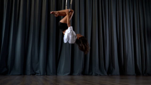 Flexible gymnast performs a trick in the aerial hoop video
