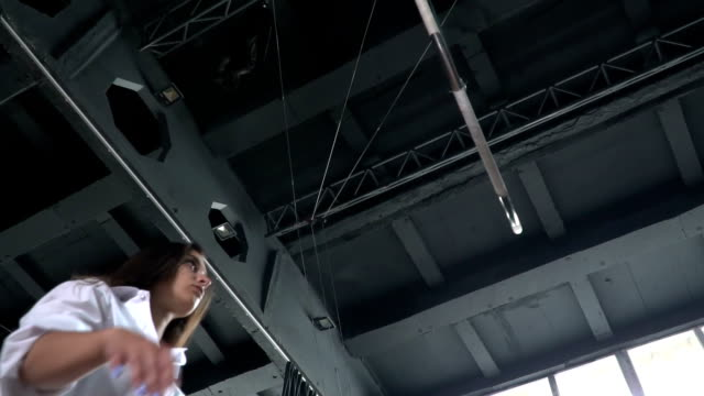 Flexible gymnast performs a trick on the aerial hoop in slowmotion video