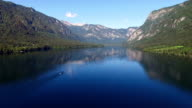 Flight above amazing Bohinj Lake in the morning. People are training in rowing. Blue deep water and Julian Alps mountains. Triglav National Park, Slovenia. video