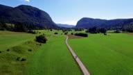 Flight above green Bohinj Lake valley in the morning. People riding bicycles on a path. Stara Fuzina village in Julian Alps. Triglav National Park, Slovenia. video