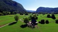 Flight above green valley near Bohinj Lake in the morning. Road to the Stara Fuzina village in Julian Alps. Triglav National Park, Slovenia. video