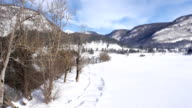 AERIAL: Flight next to the lake in snowy landscape. Reflection of the mountain in the water video