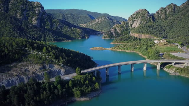 Flight over beautiful turquoise lake in mountains and several bridges across lake. video
