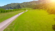Flight over cars on a winding road in the hills and meadow. Rural highway below video