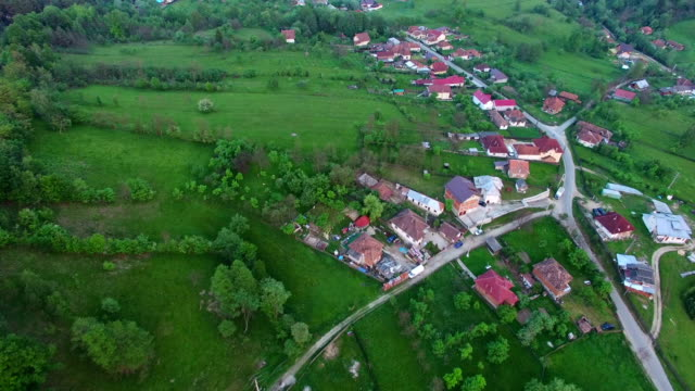 Flight over green hills and country village video