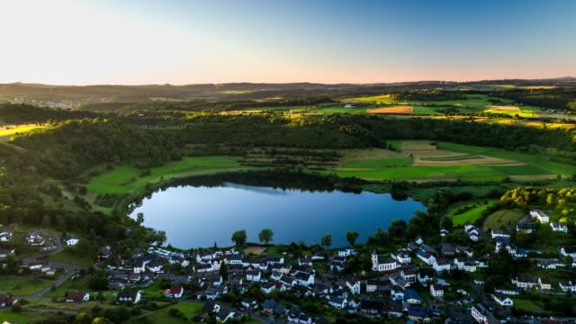 Flight over idyllic landscape with volcanic crater lake Schalkenmehrener Maar in Germany video