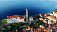 Flight over old city Piran, aerial bird's eye view with old houses, St. George's Parish Church and the sea. Slovenia. video
