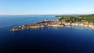 Flight over old city Piran, aerial panoramic view with old houses, St. George's Parish Church, fortress and the sea. Slovenia. video