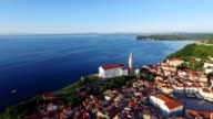 Flight over old city Piran, aerial panoramic view with old houses, St. George's Parish Church, Tartini Square, fortress and the sea. video