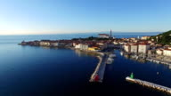 Flight over old city Piran, aerial panoramic view with St. George's Parish Church, fortress, yachts, berths and the sea. video