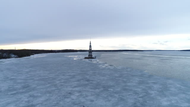 Flight over the frozen river to the bell tower video
