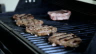 Flipping Burgers on a Grill; with Steak video