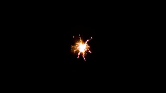 Floating burning sparkler on black background video