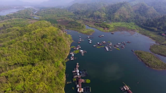 Floating houses of fisherman village in lake among the mountain, Aerial view video