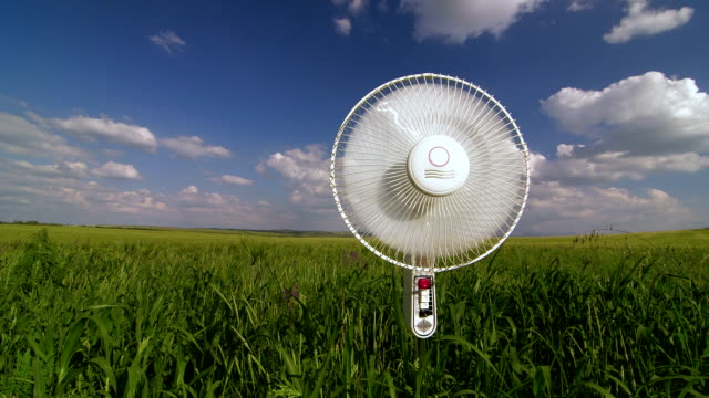 Floor electric fan standing in green field video