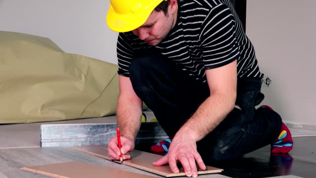 Floor laying man with pencil make markings on laminate board video