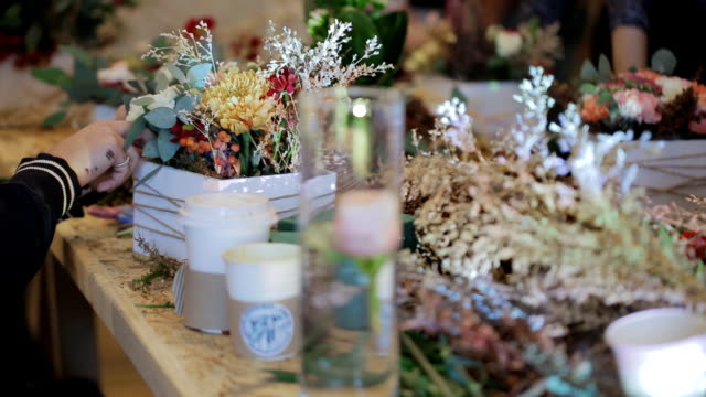 florist adds details in a pot of flowers, individual design project video