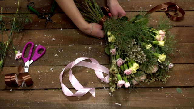 Florist at work arranging flowers into a bouquet. video
