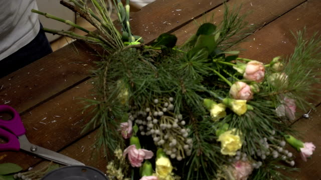 Florist at work with bouquet of flowers video