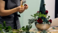 Florist creates a fresh flower arrangement with roses and eucalyptus video