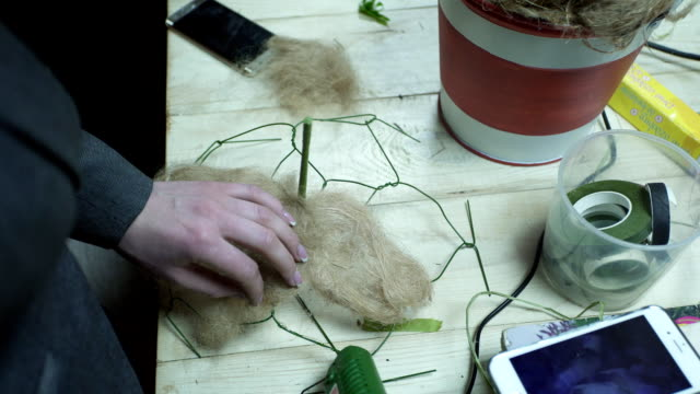 Florist deals glue gun and material basis for the floral design video