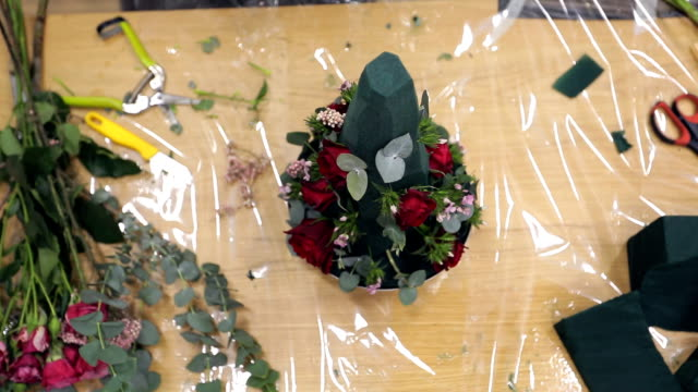 Florist decorates bouquet by greens and beautiful natural flowers video