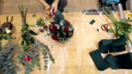 Florist decorates bouquet by pink roses with ruby color impregnations video