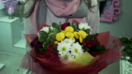 Florist demonstrates complete bouquet of flowers video