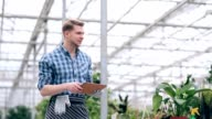 Florist keeps a record of plants in greenhouse video