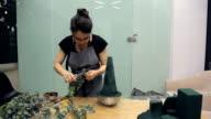 Florist removes eucalyptus branch leaves for a flower arrangement video