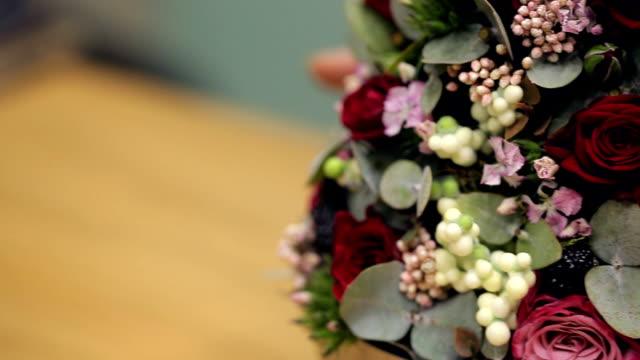 Florist shows finished flower arrangement on table inside office video