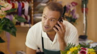 florist talking with customer on telephone and selling flowers video