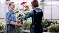 Florists fooling around while caring for flowers video