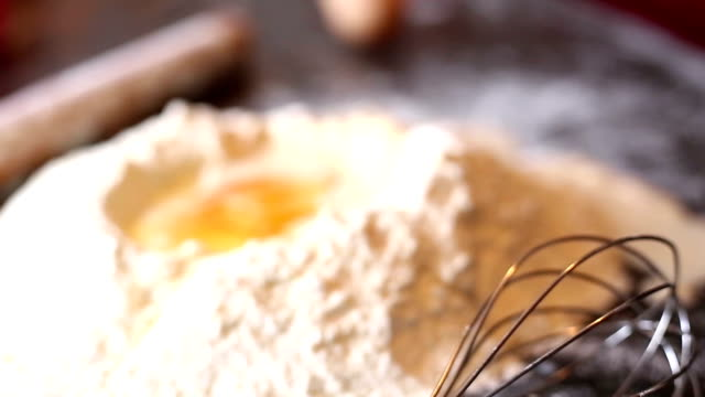 Flour in bowl with eggs and rolling pin video